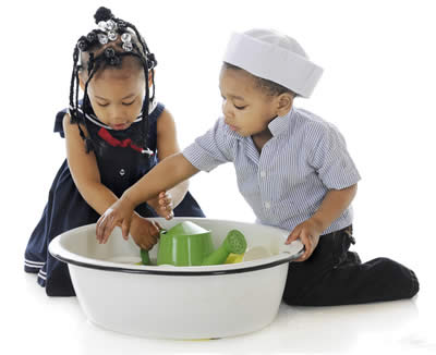 two children playing with toys in a waterbasin