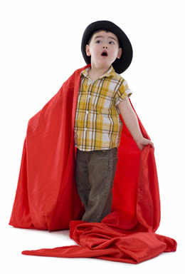 toddler with blanket cape and hat