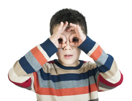 boy with hands on face making glasses
